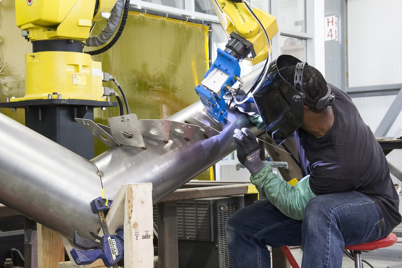 Local 2 Journeyman Keidric Rowe welds stainless steel tab while Fanuc robot holds in position