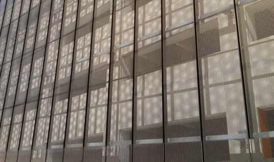 The perforated metal panel's shadow creates a moire effect against the building's surface.