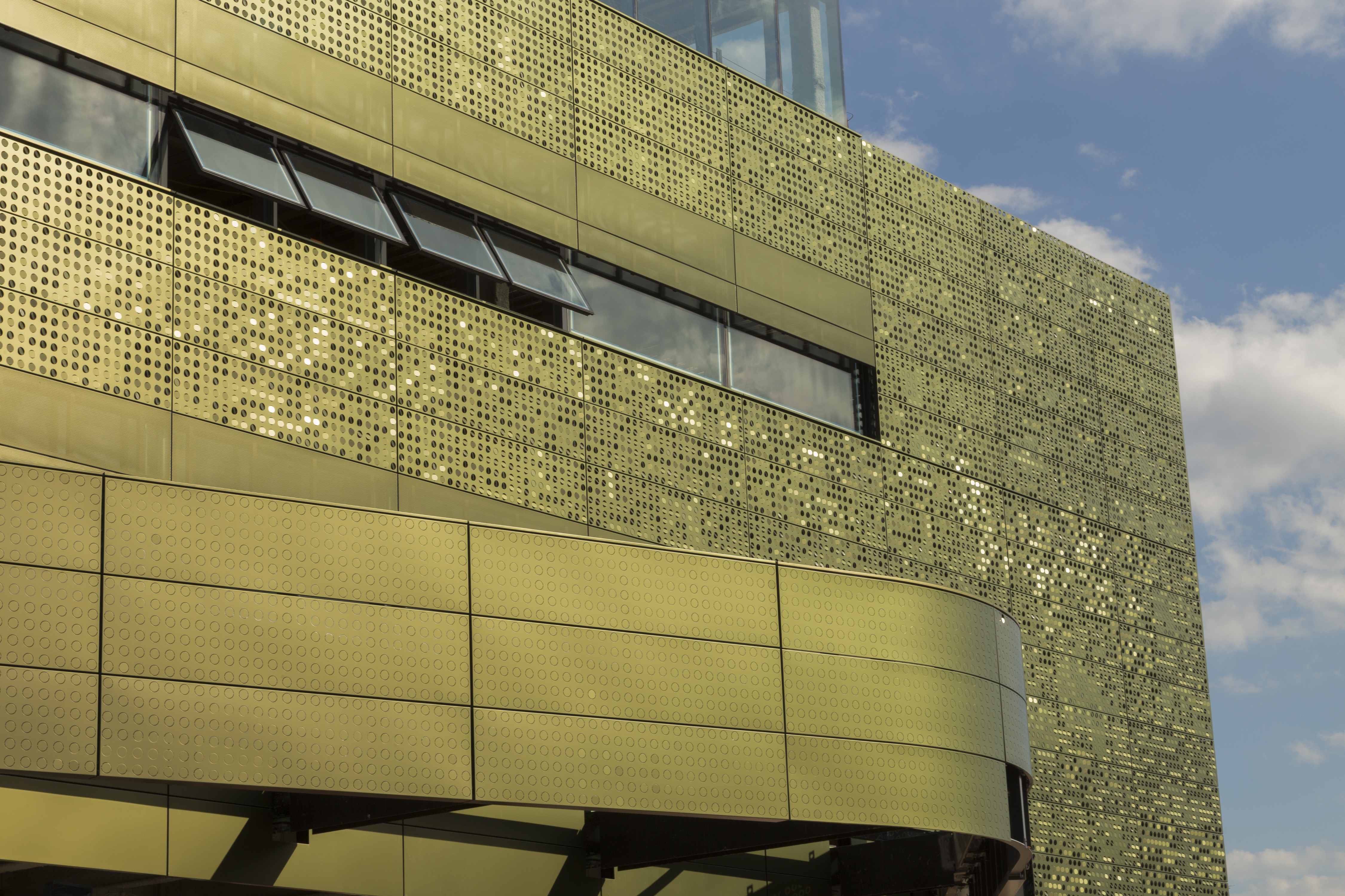 Perforation patterns on color-shift iridescent painted aluminum panels.