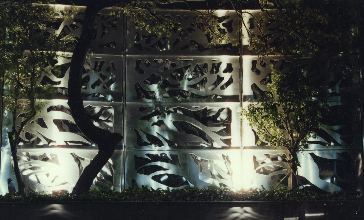 Photograph at night of the stainless steel art wall at Carmen's Garden in Hong Kong.
