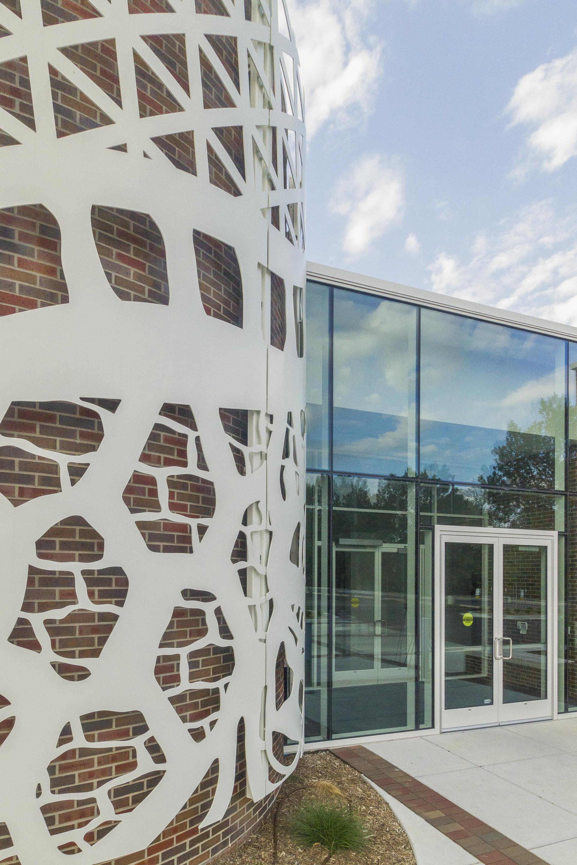 Water-jet cut aluminum facade on brick.
