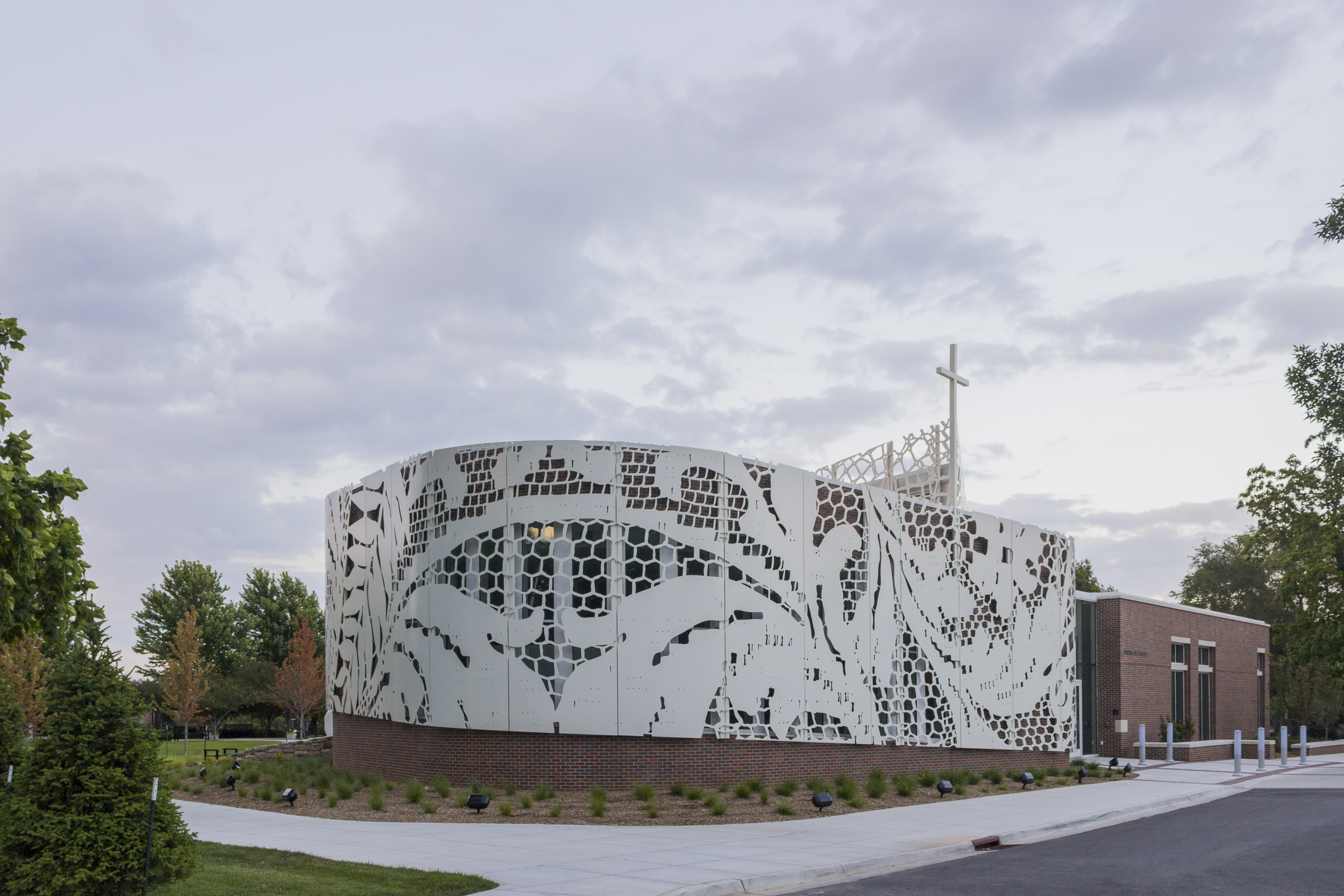Lace patterns cut into plate aluminum and rolled for the curving facade at St. Teresa's Academy.