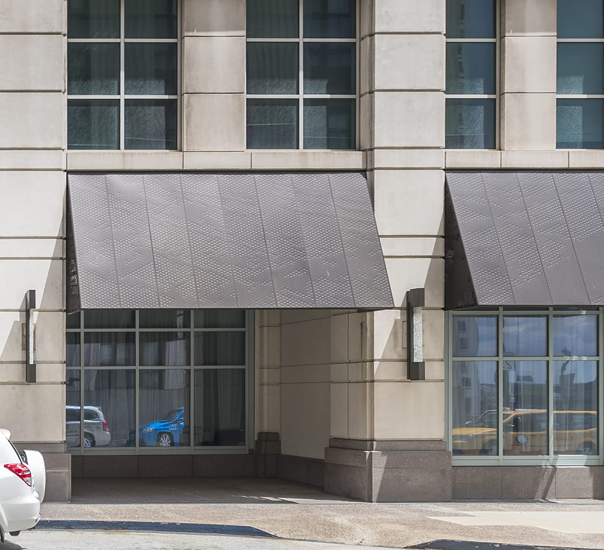 Anodized aluminum panels and structure for a series of awnings. Raised circles on the front create a pattern while still protecting from the elements.